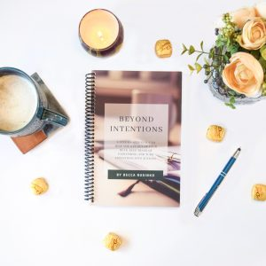 Flatlay image of the spiral-bound Beyond Intentions workbook with flowers, coffee, and a candle.