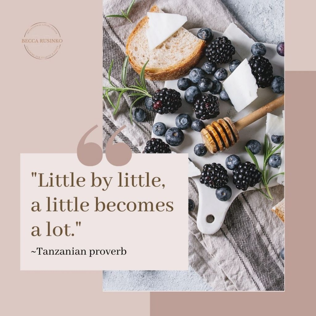 """A cutting board rests on a blue striped tea towel. Berries and rosemary are scattered across the tableau. The text reads: """"Little by little, a little becomes a lot - Tanzanian proverb"""""""