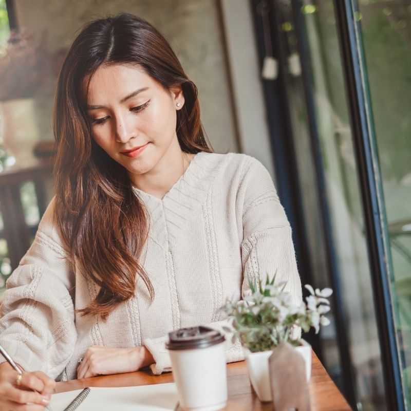 A woman sits at a cafe writing in a notebook. She has coffee in front of her, and a small vase of greenery decorates the table. She appears to be thinking about something satisfying--like living by her priorities.