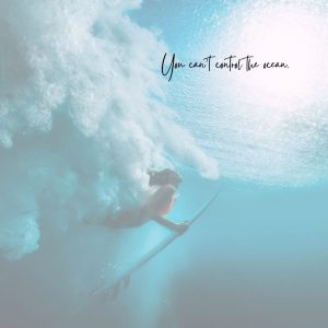 A woman holds her surfboard underwater as she rises to the surface. The text reads: You can't control the ocean.
