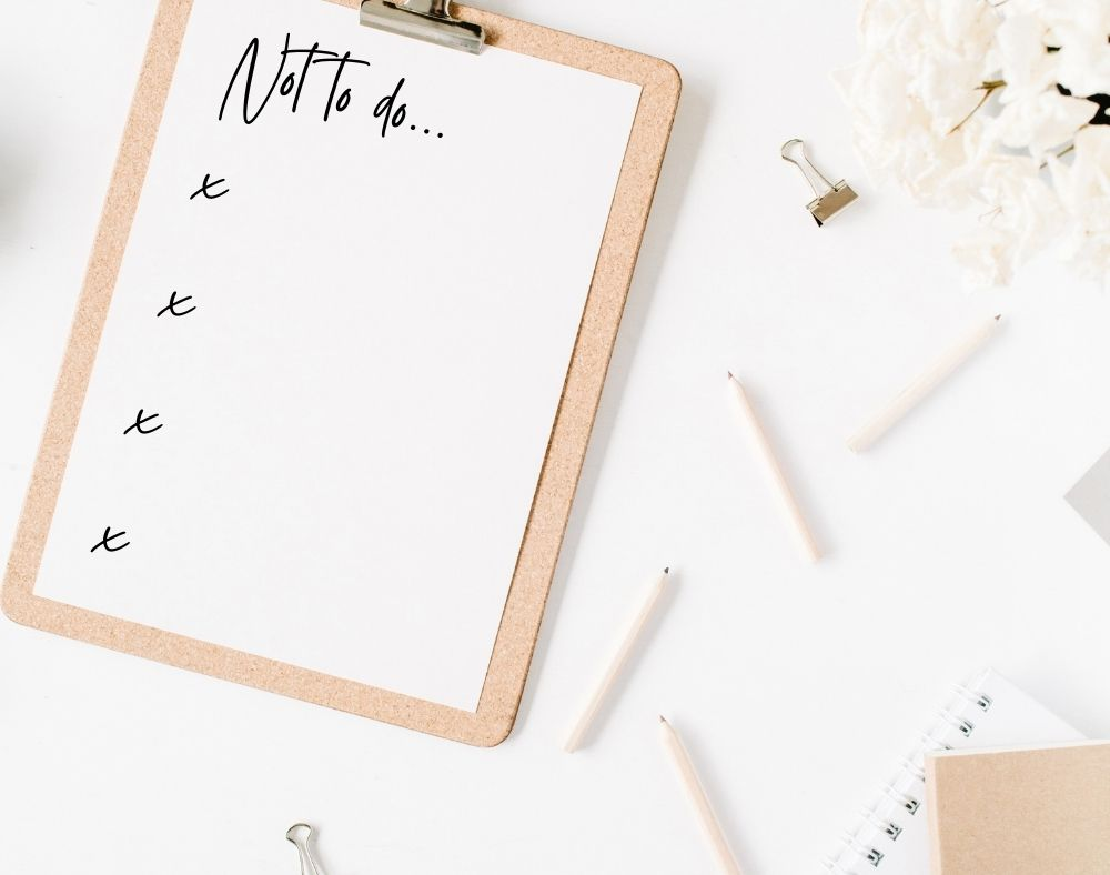 A Not-to-Do list on a clipboard sits on a desk. Pencils, flowers, and notebooks are scattered about the flatlay.