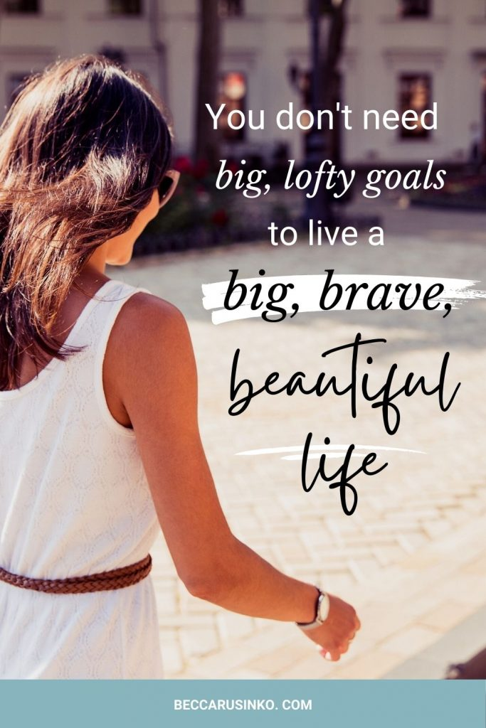 You don't need big, lofty goals to live a big, brave, beautiful life. [The decorative image shows a woman walking forward with intention. She is walking past the camera, and we can't see her face, but her body language shows momentum and purpose. She wears a stylish yet relaxed white dress, and in the background you can see a city building that appears to be old but well-maintained.]