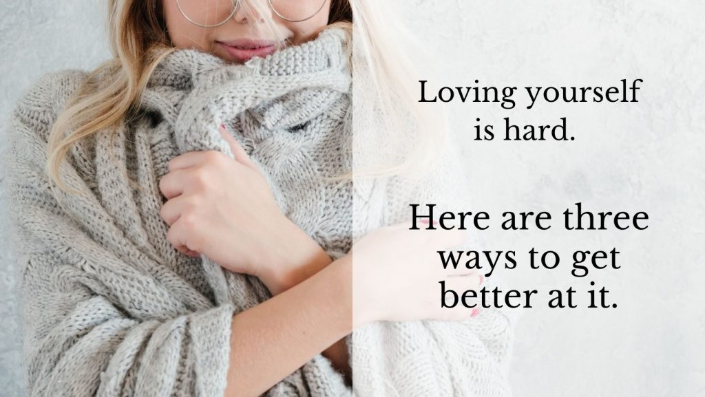 Loving yourself is hard. Here are three ways to get better at it. [The decorative background image shows a woman wrapped up in a cozy grey sweater, snuggled into herself. The photo is cropped to focus on her gentle smile and her arms. The vibe is that she is learning to be kind to herself.]