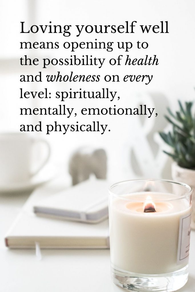 """""""Loving yourself well means opening up to the possibility of health and wholeness on every level: spiritually, mentally, emotionally, and physically. [The decorative background photo shows a lit candle and two linen-covered notebooks in focus. Behind them, slightly out of focus are a potted rosemary plant, an elephant figurine, an ampersand figurine, and a white coffee cup. Everything behind that is entirely blurred, mostly white.]"""""""
